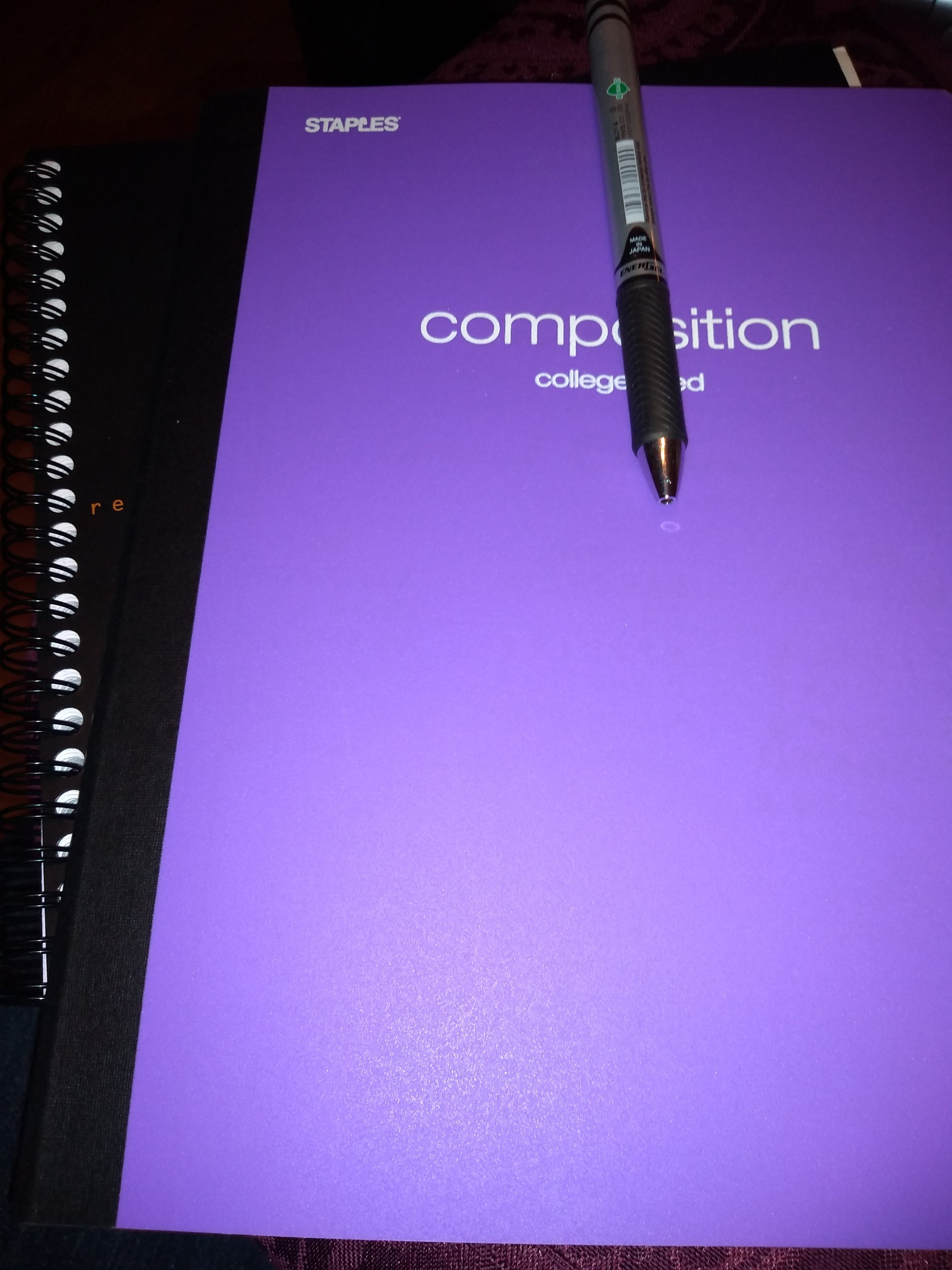 Two notebooks, one purple with a pen clipped to it and one black spiral notebook under the purple one